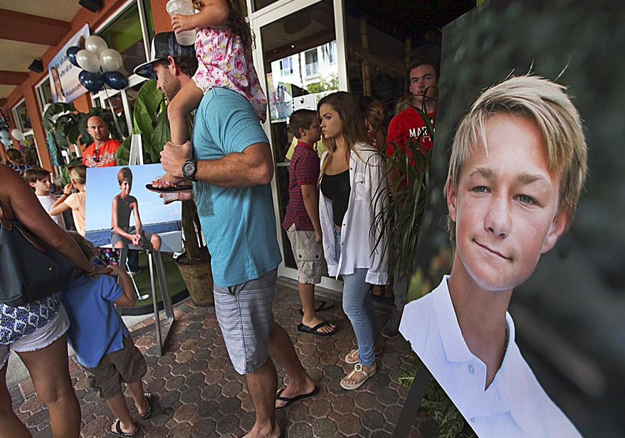 Pictures of Perry Cohen, left, and Austin Stephanos, right, are on display at fundraiser at Jumby Bay Island Grill, Wednesday, July 29, 2015, in Jupiter, Fla., during a fundraiser to pay for private search efforts for Nick Cohen and Austin Stephanos who have been missing since they took their boat out of the Jupiter Inlet Friday. (Richard Graulich/The Palm Beach Post via AP) (Richard Graulich/The Palm Beach Post via AP) ** FILE **