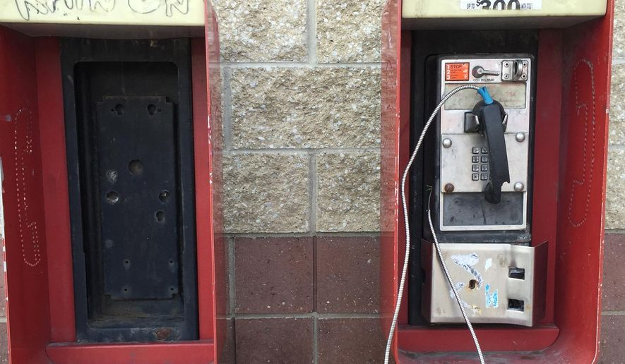 This July 1, 2015 photo shows two red pay phones outside the Shamrock gas station at Woodward and Clairmount near a bus stop in Detroit.  Like the typewriter and transistor radio, the pay phone is a once-ubiquitous facet of life whose convenience and business model was outmoded by technology.  (JC Reindl/Detroit Free Press via AP)  DETROIT NEWS OUT; TV OUT; MAGS OUT; NO SALES; MANDATORY CREDIT DETROIT FREE PRESS