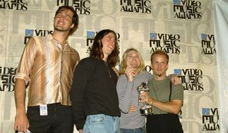 "In this Sept. 2, 1993 file photo, Nirvana band members, Chris Novoselic, from left, Dave Grohl, and Kurt Cobain pose, with an unidentified man, right, after receiving an award for best alternative video for ""In Bloom"" at the 10th annual MTV Video Music Awards in Universal City, Calif. (AP Photo/Mark J. Terrill, File)"