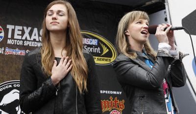 """Sadie Robertson of """"Duck Dynasty"""" holds her hand to her heart as her aunt Missy Robertson sings the national anthem before the start of a rain-delayed NASCAR Sprint Cup Series auto race at Texas Motor Speedway in Fort Worth. (AP Photo/Mike Stone)"""