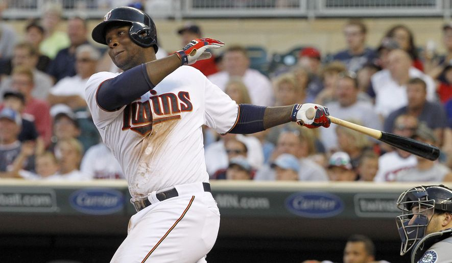 Minnesota Twins'  Miguel Sano follows through on a solo home run off Seattle Mariners starting pitcher Taijuan Walker during the fourth inning of a baseball game in Minneapolis, Friday, July 31, 2015. (AP Photo/Ann Heisenfelt)
