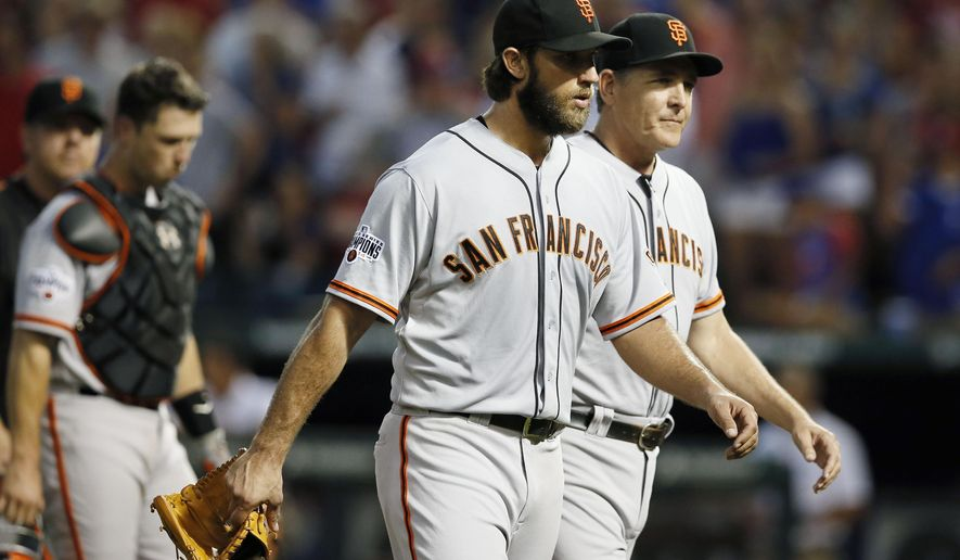 San Francisco Giants starting pitcher Madison Bumgarner is escorted back to the dugout by a member of the staff after a heated exchange between Gardner and members of the Texas Rangers in the fourth inning of a baseball game Friday, July 31, 2015, in Arlington, Texas. Both benches cleared the dugouts and met on the field but promptly returned to their respective dugouts. (AP Photo/Tony Gutierrez)