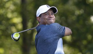 Tiger Woods watches his tee shot on the 13th hole during the second round of the Quicken Loans National golf tournament at the Robert Trent Jones Golf Club in Gainesville, Va., Friday, July 31, 2015.  (AP Photo/Steve Helber)