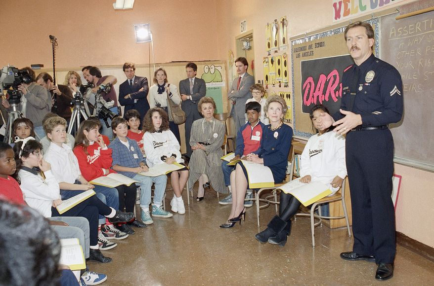 First lady Nancy Reagan sits with students at Rosewood Elementary School in Los Angeles on Feb. 10, 1987, as they listen to a presentation by Los Angeles police Officer Greg Boles. The presentation was part of Los Angeles Police Department's Project D.A.R.E. (Drug Abuse Resistance Education). (Associated Press)