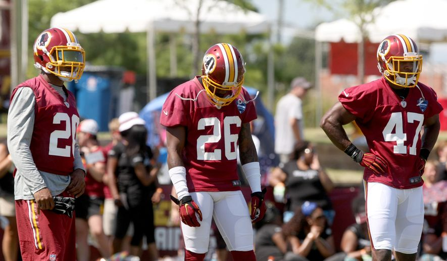 Washington Redskins cornerback Bashaud Breeland (26), center, defensive back Jeron Johnson, left, and defensive back Akeem Davis go through offensive drills during an NFL football training camp in Richmond, Va., Friday, July 31, 2015. Breeland was suspended Friday by the NFL for violating the leagues substance abuse policy. (AP Photo/Jason Hirschfeld)