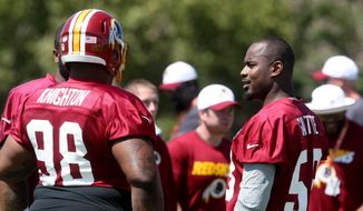 Washington Redskins defensive tackle Terrance Knighton, left, talks with newly signed teammate Junior Galette, right, during the teams NFL football training camp in Richmond, Va., Friday, July 31, 2015.  (AP Photo/Jason Hirschfeld)