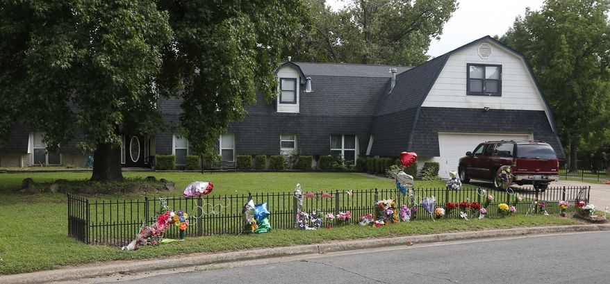 A memorial with flowers and balloons at the fence of the Bever home in Broken Arrow, Okla., is pictured Thursday, July 30, 2015, a week after five family members were found murdered at the home. Neighbors in this quiet Tulsa suburb are still coming to grips with how such brutality could happen here. (AP Photo/Sue Ogrocki)