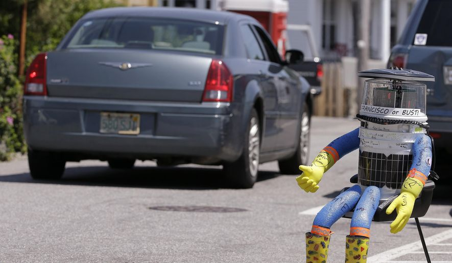 In this July 17, 2015, file photo, a car drives by HitchBOT, a hitchhiking robot in Marblehead, Mass. The Canadian researchers who created hitchBOT as a social experiment say someone in Philadelphia damaged the robot beyond repair on Saturday, Aug. 1, ending its brief American tour. The robot was trying to travel cross-country after successfully hitchhiking across Canada last year and parts of Europe. (AP Photo/Stephan Savoia, File)