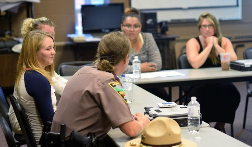 In this July 27, 2015 photo, Trooper Cortney Paul discusses her role as a trooper for the South Dakota Highway Patrol during a recruiting seminar in Sioux Falls, S.D. Paul spoke to a group of women during a seminar hosted by the patrol in an effort to bring more women onto the force, which currently only has five active female troopers. (AP Photo/Kevin Burbach)