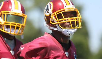 Washington Redskins cornerback Bashaud Breeland, right, smiles during the team's NFL football training camp in Richmond, Va., Friday, July 31, 2015. Breeland was suspended without pay for one game by the NFL on Friday, nearly a full year after he was cited for marijuana possession. (AP Photo/Jason Hirschfeld)