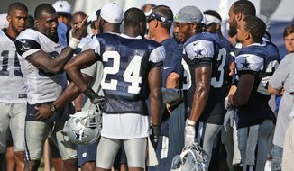 Separated by teammates, Dallas Cowboys wide receiver Dez Bryant, left, confronts defensive back Tyler Patmon, far right, after a rough play during the Cowboys afternoon practice at their 2015 training camp in Oxnard, Calif., Sunday, Aug. 2, 2015. (Paul Moseley/Star-Telegram via AP)