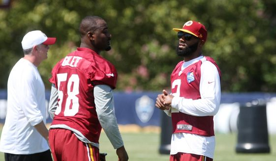 Washington Redskins cornerback DeAngelo Hall, right, talks with teammate Junior Galette during the teams NFL football training camp in Richmond, Va., Saturday, Aug. 1, 2015. (AP Photo/Jason Hirschfeld)