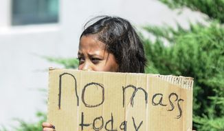 Aaliyah Doninguez, 11, stands on North Alameda Boulevard on Sunday, Aug. 2, 2015, in Las Cruces, N.M., advising parishioners that Holy Cross Catholic Church Mass is canceled. Churchgoers were left shaken during Sunday morning services after authorities say explosions occurred less than 30 minutes apart outside two Las Cruces churches. (Robin Zielinski/The Las Cruces Sun-News via AP)