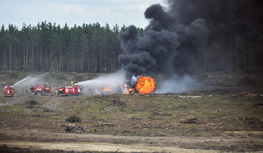 Firefighters extinguish a burning Russian military helicopter after it crashed during an aerobatic display in Dubrovichi, Russia, Sunday, Aug. 2, 2015, killing one of its crew members and injuring another. The Mi-28 helicopter gunship was part of a flight of helicopters performing aerobatics at the Dubrovichi firing range in Ryazan region, about 170 kilometers (105 miles) southeast of Moscow, when it crashed Sunday. (Anton Nasonov, RZN.info/Photo via AP)
