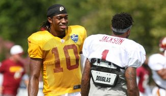 Washington Redskins quarterback Robert Griffin III, left, and wide receiver DeSean Jackson, right, talk during the team's NFL football training camp in Richmond, Va., Monday, Aug. 3, 2015.   (AP Photo/Jason Hirschfeld)