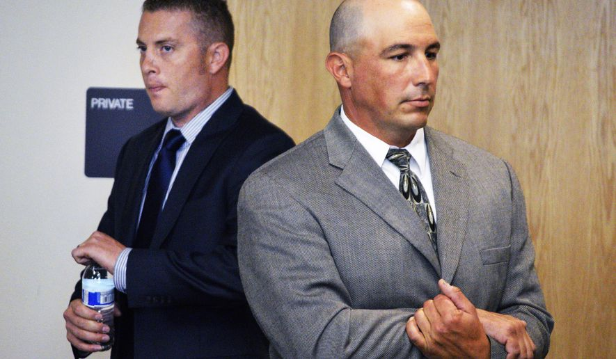 Albuquerque officer Dominique Perez, left, and former Albuquerque Detective Keith Sandy, right, stand up in court after listening to a special prosecutor tell a judge at a preliminary hearing in Albuquerque that they unlawfully shot a homeless camper who posed no threat in  Albuquerque, N.M. on Monday, Aug. 3, 2015. Sandy and Perez are facing second-degree murder charges in the 2014 fatal shooting death of 38-year-old James Boyd. (AP Photo/Russell Contreras)