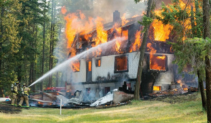 A pair of Whitefish firefighters work to contain a house fire on Trumble Creek Road in rural Columbia Falls, Mont., Monday, Aug. 3, 2015. (Chris Peterson/Hungry Horse News via AP) MANDATORY CREDIT