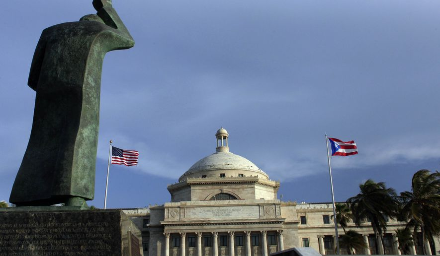 A bronze statue of San Juan Bautista stands in front of Puerto Rico's Capitol in San Juan as U.S. and Puerto Rican flags fly on July 29, 2015. Mired in an ongoing economic crisis the government has tried to boost revenue by hiking the sales tax to 11.5 percent, higher than any U.S. state, and closing government offices. (Associated Press) **FILE**