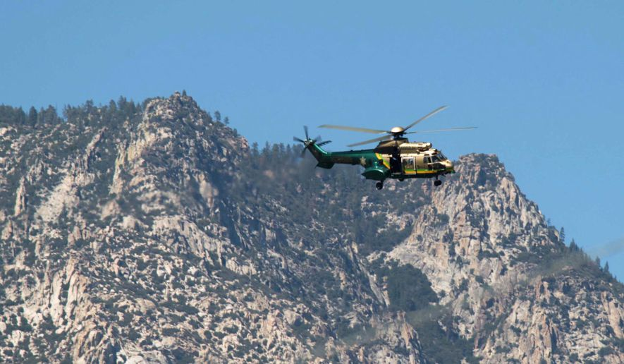 In this Sunday, Aug. 2, 2015 photo, a Los Angeles County Sheriff's helicopter flies near Weldon, Calif. Authorities searched an area east of Bakersfield, Calif., on Monday, Aug. 3, as part of a six-day manhunt involving the wounding of the deputies. (Casey Christie/The Bakersfield Californian via AP)  MANDATORY CREDIT; MAGS OUT; NO SALES; ONLINE OUT; TV OUT