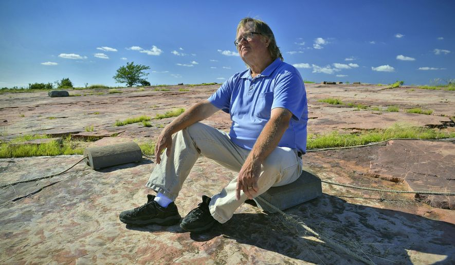 This July 21, 2015, photo shows Tom Sanders, site manager at Jeffers Petroglyphs historic site, talking about the 5,000 or so ancient carvings that have been found etched into the stone at the site near the southwest Minnesota town of Comfrey. (Kimm Anderson/St. Cloud Times via AP)