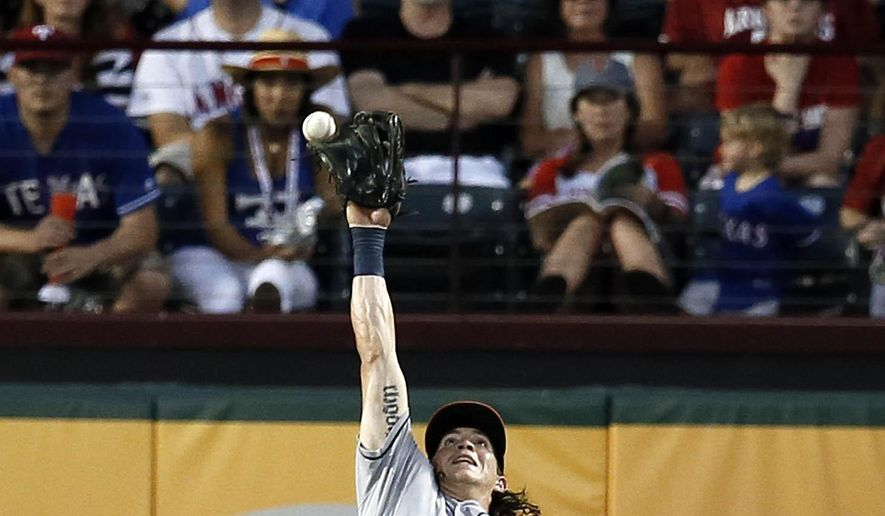 Fans look on as Houston Astros right fielder Colby Rasmus (28) has the ball go off the top of his glove giving a double to Texas Rangers' Shin-Soo Choo in the fourth inning of a baseball game Tuesday, Aug. 4, 2015, in Arlington, Texas. (AP Photo/Tony Gutierrez)