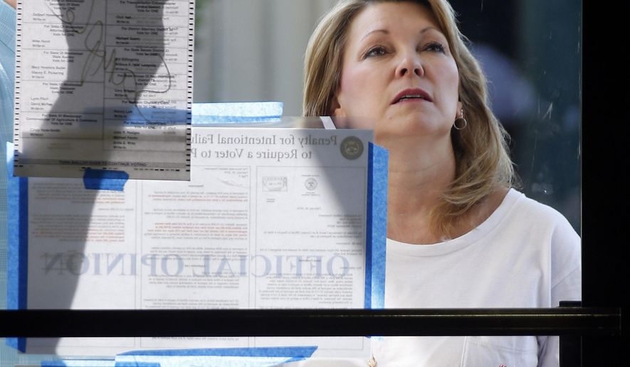 Amanda Hutchison reviews the list of candidates that her husband, Mark, points out on the ballot prior to entering a Madison, Miss., poll, Tuesday, Aug. 4, 2015. Voters are choosing Democratic and Republican nominees for governor and lieutenant governor as well as other statewide, county and some city offices. (AP Photo/Rogelio V. Solis)