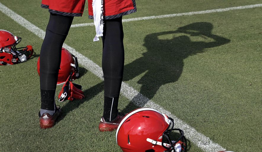 North Carolina State wide receiver Elliott Davis puts on his helmet at the start the team's first NCAA college football practice of the season in Raleigh, N.C., Tuesday, Aug. 4, 2015. (AP Photo/Gerry Broome)
