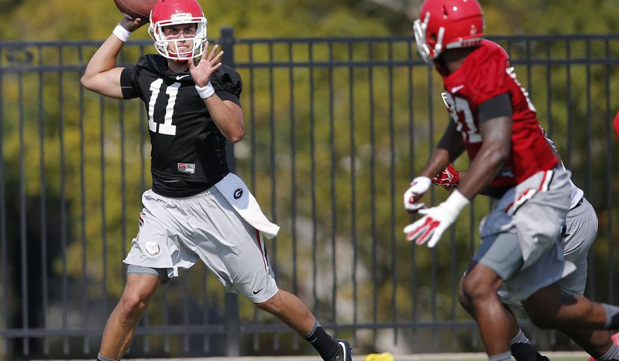 Georgia quarterback Greyson Lambert (11) throws under pressure from  linebacker John Huff (57) during a college football practice Tuesday, Aug. 4, 2015, in Athens, Ga. Georgia's quarterback competition is getting crowded for the start of practice, with Virginia transfer Greyson Lambert joining Brice Ramsey and Faton Bauta. (AP Photo/John Bazemore)