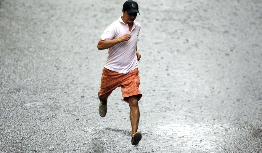 A pedestrian runs through heavy rain during a severe thunderstorm in Boston, Tuesday, Aug. 4, 2015. A line of powerful thunderstorms rolled through communities in southern New England on Tuesday, toppling trees that killed a driver and injured several campers at a state park and leaving as many as 150,000 electric customers without power at the height of the storms. (AP Photo/Michael Dwyer)