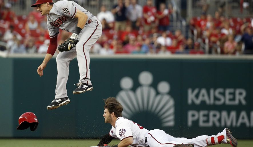 Arizona Diamondbacks shortstop Nick Ahmed comes down after jumping up in attempt to field the throw to second from the outfield, but Washington Nationals' Bryce Harper (34) was safe at second base with a double during the first inning of a baseball game at Nationals Park, Tuesday, Aug. 4, 2015, in Washington. (AP Photo/Alex Brandon)