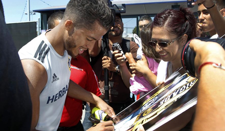 Los Angeles Galaxy forward Giovani dos Santos signs autographs after his first training with the MLS soccer team in Carson, Calif., on Tuesday, Aug. 4, 2015. After four years of courting dos Santos, the Galaxy signed the highest-profile Mexican star in their history to a designated player contract, paying a reported $7 million transfer fee. He will make his Major League Soccer debut on Sunday against the Seattle Sounders FC. (AP Photo/Nick Ut)
