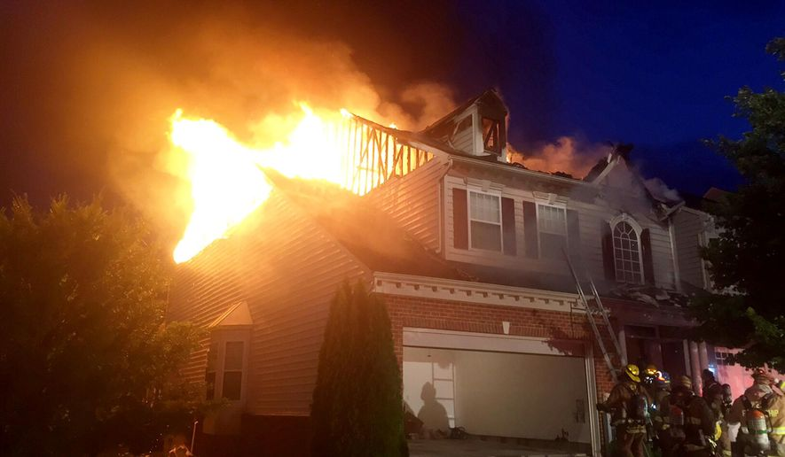 In a Tuesday, Aug. 4, 2015 photo provided by the Howard County Department of Fire & Rescue, firefighters work to contain a single family house fire in Marriottsville, Md. High winds, downed trees and wires and lightning is being blamed for the house fire, as severe storms raced through the mid-Atlantic region. (Doug Walton/Howard County Department of Fire & Rescue  via AP) MANDATORY CREDIT