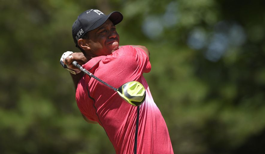 Tiger Woods watches his tee shot on the 15th tee during the final round of the Quicken Loans National golf tournament at the Robert Trent Jones Golf Club in Gainesville, Va., Sunday, Aug. 2, 2015. (AP Photo/Nick Wass)
