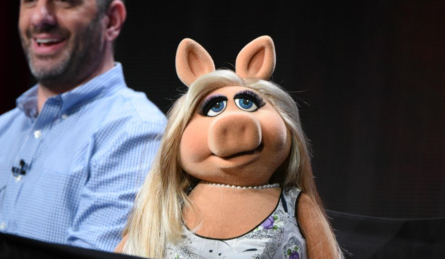 """Miss Piggy participates in """"The Muppets"""" panel at the Disney/ABC Summer TCA Tour at the Beverly Hilton Hotel on Tuesday, Aug. 4, 2015, in Beverly Hills, Calif. Looking on at left is writer/executive producer Bob Kushell. (Photo by Richard Shotwell/Invision/AP)"""