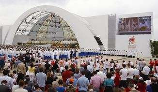 Faithful gather in Bresso, near Milan, Italy, to follow a Mass celebrated by Pope Benedict XVI in this Sunday, June 3, 2012, file photo. (AP Photo/Antonio Calanni/File)