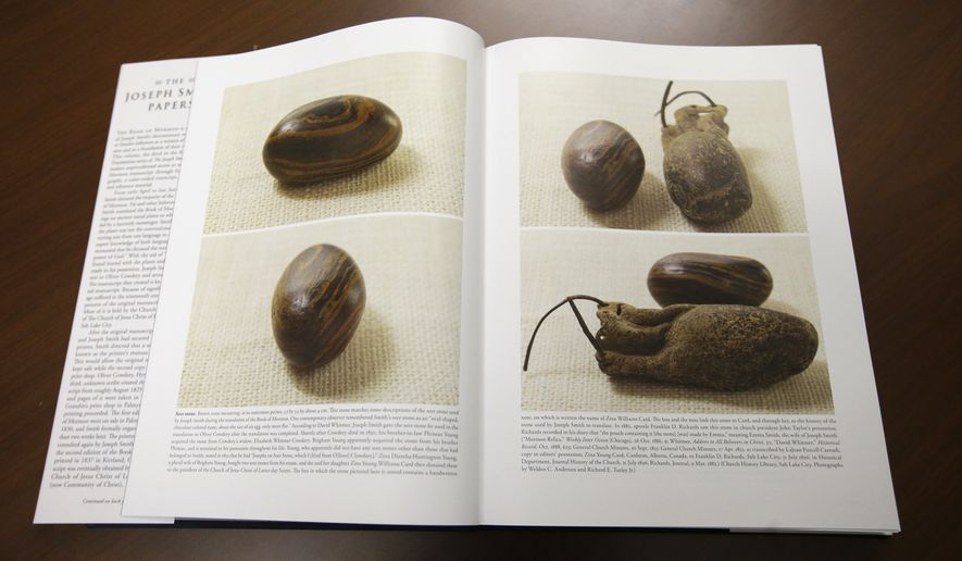 Pictures of a smooth, brown, egg-sized rock are shown in the printer's manuscript of the Book of Mormon following a news conference Tuesday, Aug. 4, 2015, at the Church of Jesus Christ of Latter-day Saints Church History Library, in Salt Lake City. The Mormon church for the first time is publishing photos of a small sacred stone it believes founder Joseph Smith used to help translate the story that became the basis of the religion. The Mormon church is taking another step in its push to be more transparent, and is releasing more historical documents that shed light on how Joseph Smith formed the religion. (AP Photo/Rick Bowmer)