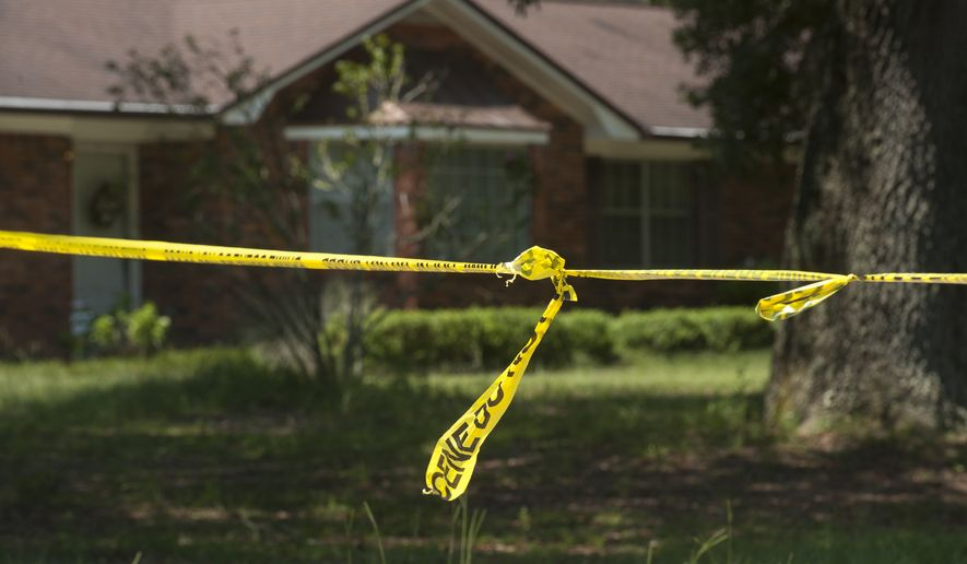 In this Monday, Aug. 3, 2015 photo, investigative tape is seen near a home in Pensacola, Fla. A triple homicide in Florida is being investigated as a possible ritualistic killing connected to the recent blue moon, Escambia County Sheriff David Morgan said Tuesday, Aug. 4. (Tony Giberson/The Pensacola News Journal via AP)  NO SALES; MANDATORY CREDIT