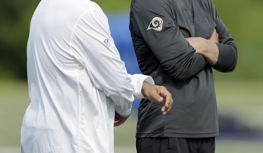 St. Louis Rams head coach Jeff Fisher, left, and general manager Les Snead chat as they watch during training camp at the NFL football team's practice facility Tuesday, Aug. 4, 2015, in St. Louis. (AP Photo/Jeff Roberson)