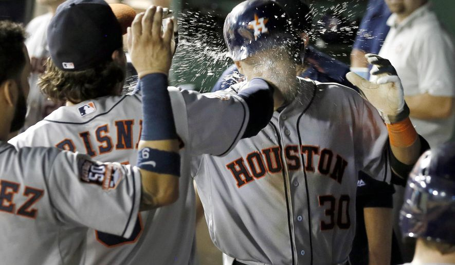 Houston Astros' Jake Marisnick, left, splashes a glass of water to the face of Carlos Gomez as the dugout celebrates Gomez' solo home run against the Texas Rangers in the sixth inning of a baseball game Tuesday, Aug. 4, 2015, in Arlington, Texas. (AP Photo/Tony Gutierrez)