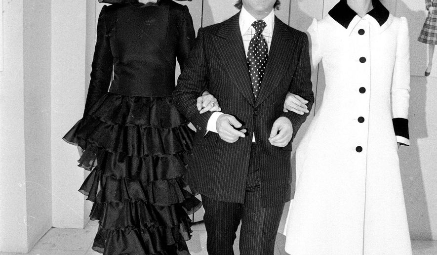 FILE - In this April 28, 1972 file photo, American designer Arnold Scaasi, center, walks with two models at his studio in Paris.  Scaasi, whose flamboyant creations adorned first ladies, movie stars and socialites, died Tuesday, Aug. 4, 2015, at New York-Presbyterian Hospital of cardiac arrest. He was 85. (AP Photo/Alison Lerrick, File)
