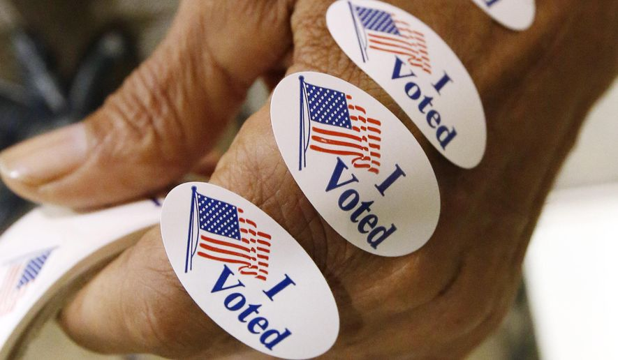 "Bailiff Garrett Cole of Madison, Miss., has ""I voted"" stickers ready to distribute to all who exit the voting booths. (AP Photo/Rogelio V. Solis)"