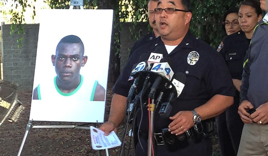 Los Angeles Police Department Cmdr. Dennis Kato, right, shows a photograph of Special Olympics athlete Sihon Ange Ismael Kone, 15, a table-tennis player from the Ivory Coast, Monday, Aug. 3, 2015, in Los Angeles. Sihon Ange Ismael Kone, who vanished from Los Angeles International Airport, was found sleeping on a lawn five miles away Monday afternoon. (AP Photo/Linda S. Zhang)