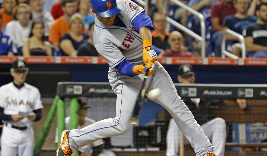 New York Mets' Juan Lagares hits a two-run triple in the eighth inning against the Miami Marlins during a baseball game in Miami, Tuesday Aug. 4, 2015. Lagares later scored on a double by Curtis Granderson. (AP Photo/Joe Skipper)