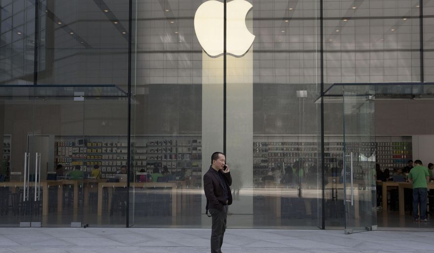 FILE - In this April 22, 2014 file photo, a man uses his phone near an Apple store in Beijing. Apple Inc., the world's most valuable public company, saw its stock price drop for a fifth straight day on Tuesday, Aug. 4, 2015, as investors fretted over China's economy and whether Apple can keep growing at the pace it's maintained over the last few quarters. (AP Photo/Ng Han Guan, File)