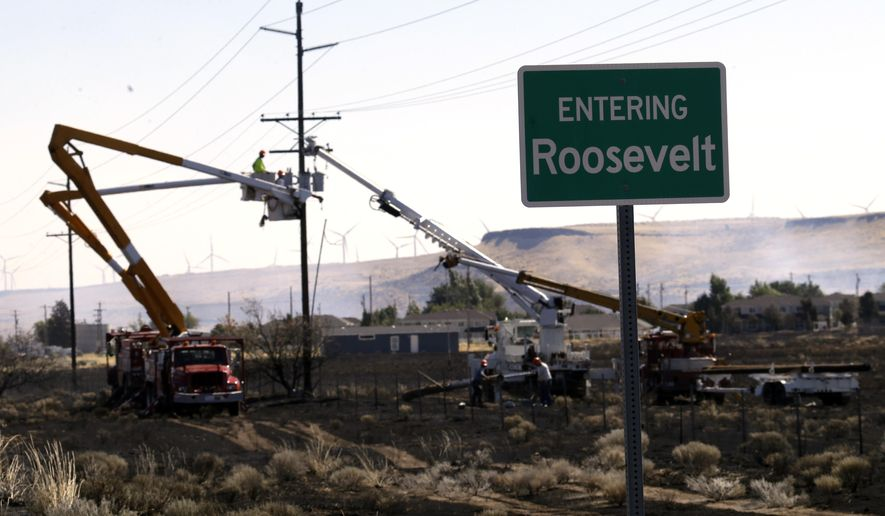 A crew works on a damaged line as blackened ground shows how close an overnight wildfire came to the town of Roosevelt, Wash., Wednesday, Aug. 5, 2015.   Residents evacuated overnight but have returned to their homes and the fire is headed away from the town. (AP Photo/Don Ryan)