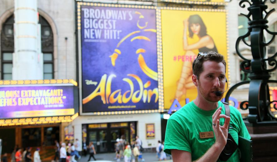 In this July 24, 2015 photo, Broadway Up Close walking tour founder Tim Dolan tells visitors about the New Amsterdam Theatre in New York. His tour is one of a handful that offer theater lovers a lively look at the history of Broadway and Times Square. (AP Photo/Mark Kennedy)