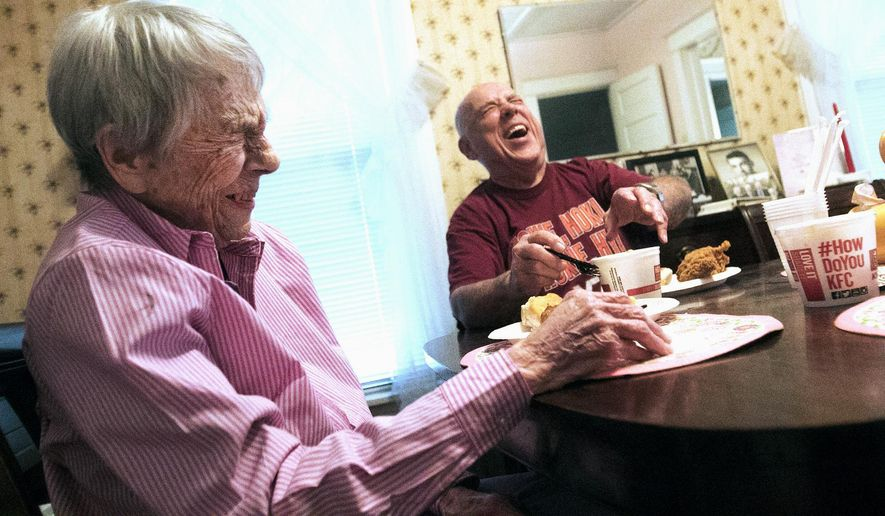"In this June 22, 2015 photo, Katheryn ""Kay"" Lyman, 99, laughs with her nephew Bill Raynolds, of Hampton, Va., as he has lunch with her in her DeKalb, Ill,, home with another niece and nephew. The three visit Aunt Kay at least once a year and bring along her favorite lunch, KFC chicken.  Lymen has four kids, 15 grandchildren, 22 great-grandchildren, and 3 great-great-grandchildren, spread out all around the country. (Danielle Guerra/Daily Chronicle via AP)  CHICAGO TRIBUNE OUT, MANDATORY CREDIT"