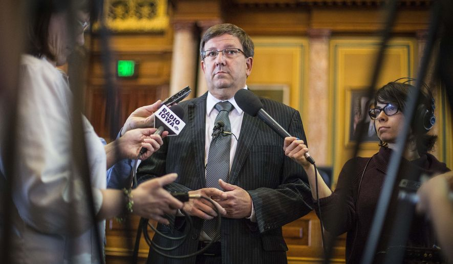 Iowa House statehpuse Speaker Kraig Paulsen, center, speaks to reporters in the Statehouse House Chambers Wednesday, Aug 5, 2015, in Des Moines, announcing he will step down as Speaker of the House  in January and not seek re-election in 2016. He will serve the rest of his two-year term, which runs through 2016. (Rodney White/The Des Moines Register via AP)  MAGS OUT, TV OUT, NO SALES, MANDATORY CREDIT