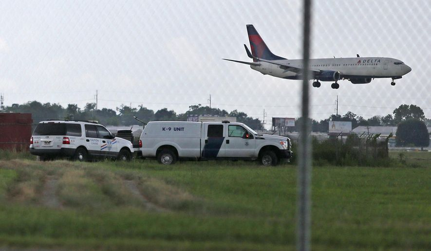 A Delta flight passes over K-9 officers with the Jefferson Parish Sheriff's Office after a drunk driver crashed through two fences at Louis Armstrong New Orleans International Airport and abandoned his blue Dodge Challenger on a runway on Wednesday, Aug. 5, 2015. Kaleb Clement, 23, of Paulina, Louisiana was arrested after a short chase. There were no injuries reported. (Michael DeMocker/The Times-Picayune via AP) NO MAGS, NO SALES, NO TV, USA TODAY OUT, NEW ORLEANS ADVOCATE OUT