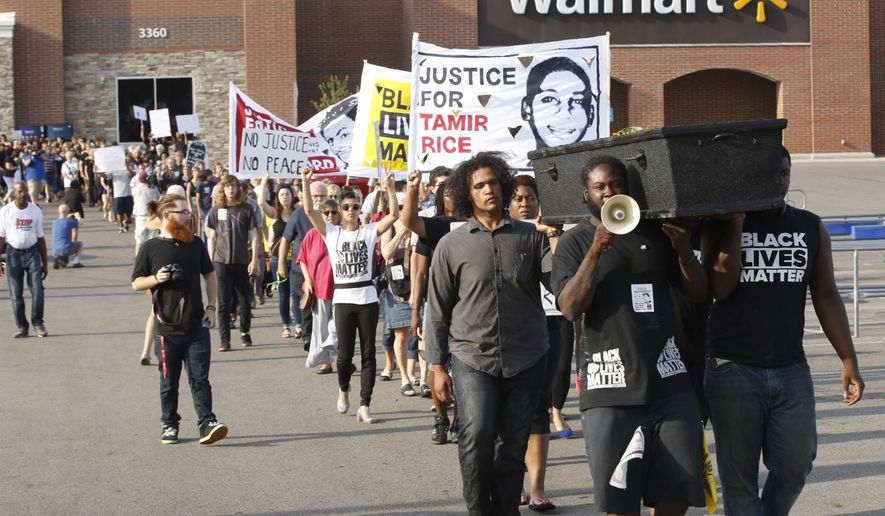 John Crawford III supporters rally in front of the Beavercreek, Ohio, Walmart on Wednesday, Aug. 5, 2015 to mark one year since a white police officer fatally shot him while holding an air rifle inside the store. (Ty Greenlees/The Dayton Daily News via AP) LOCAL PRINT OUT; LOCAL TELEVISION OUT; WKEF-TV OUT; WRGT-TV OUT; WDTN-TV OUT